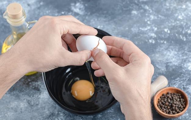 Mains d'homme cassant des œufs dans un bol sur une table grise.