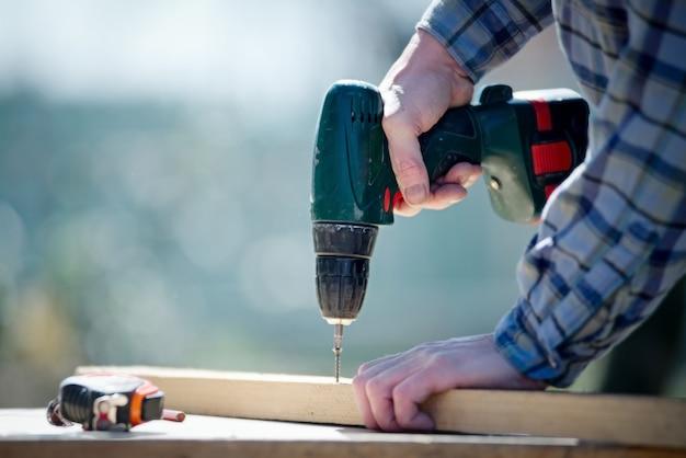 Mains d'un homme charpentier constructeur travaillant avec un tournevis électrique