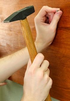 Mains d'homme avec clou et marteau