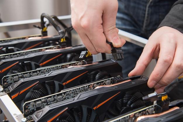 Mains d'homme connectant une nouvelle carte graphique à une ferme minière. equipement it. entreprise de crypto-monnaie.