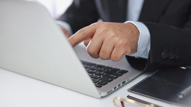 Mains d'homme en costume noir assis et utilisant un ordinateur pour le paiement en ligne ou les achats en ligne. homme d'affaires touchant le moniteur tout en travaillant. concept e-banking