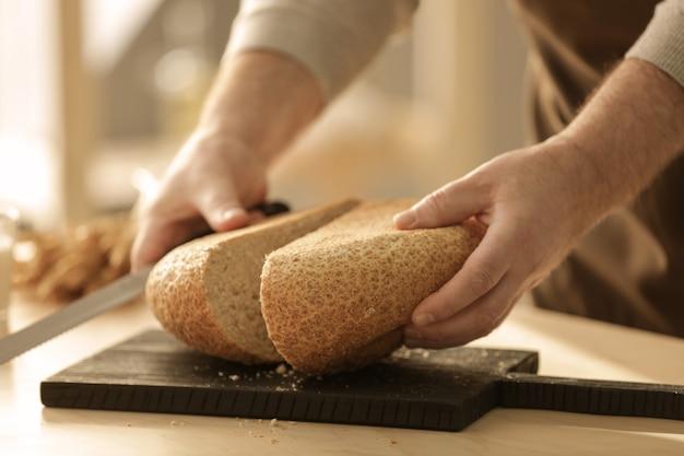 Mains d'homme coupant du pain sur la table de la cuisine