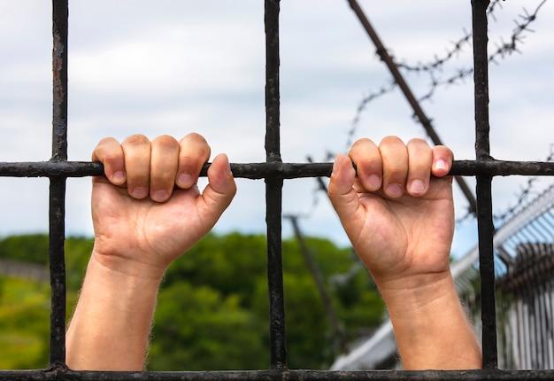 Mains d'un homme derrière les barreaux