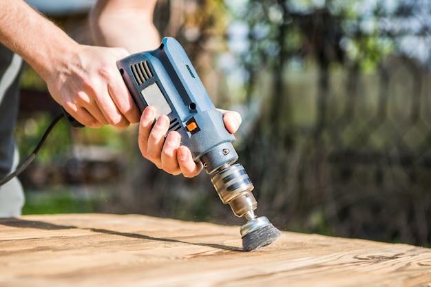 Mains homme avec disque métallique brosse rotative électrique ponçage d'un morceau de bois. travail du bois à l'extérieur.