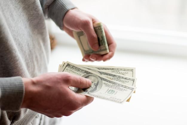 Les mains de l'homme avec des dollars sur fond blanc.
