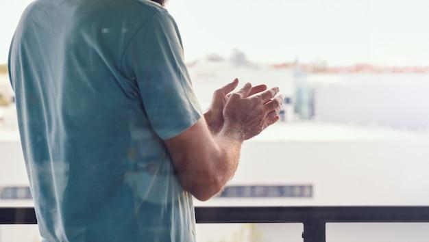 Les mains de l'homme écrasant la fenêtre par une journée ensoleillée pendant l'isolement de l'espagne par le coronavirus, vu à travers une vitre