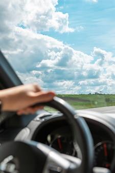Les mains de l'homme sur l'espace de copie de jour ensoleillé nuageux au volant