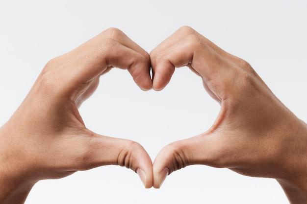 Mains d'homme faisant une forme de coeur sur un fond blanc isolé