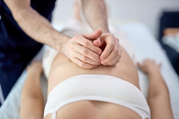 Mains d'homme faisant un massage sur une femme enceinte, allongée sur le lit