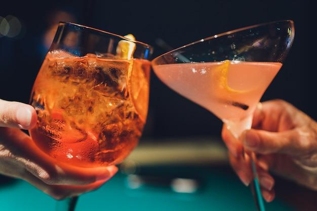 Mains d'homme et femme acclamant avec des verres de champagne rose.