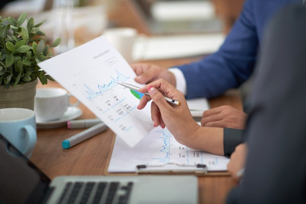 Mains d'homme et femme en tenue professionnelle assis au bureau dans le bureau et en discutant graphique