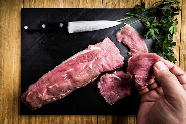 Les mains d'un homme fendant un filet de porc avec un couteau à côté de quelques branches de persil