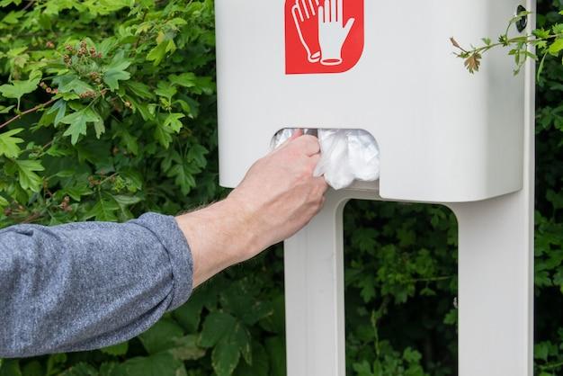 Mains de l'homme en gants de cellophane.