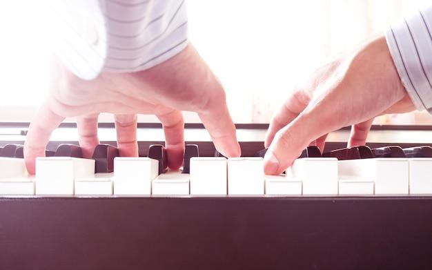 Mains d'homme jouant du piano. musique classique. art et abstrait.