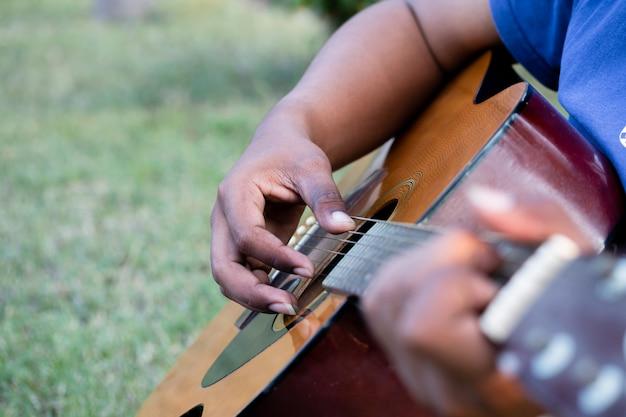 Mains d'homme jouant de la guitare acoustique, soft focus.