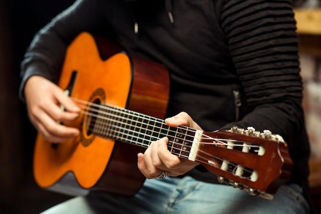 Mains d'homme jouant de la guitare. guitariste tenant une guitare acoustique.