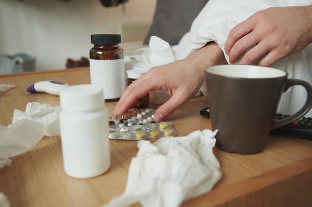 Mains d'homme malade prenant des comprimés de table alors qu'il était assis sur un lit ou un canapé à proximité et en choisissant des antipyrétiques parmi une variété de médicaments