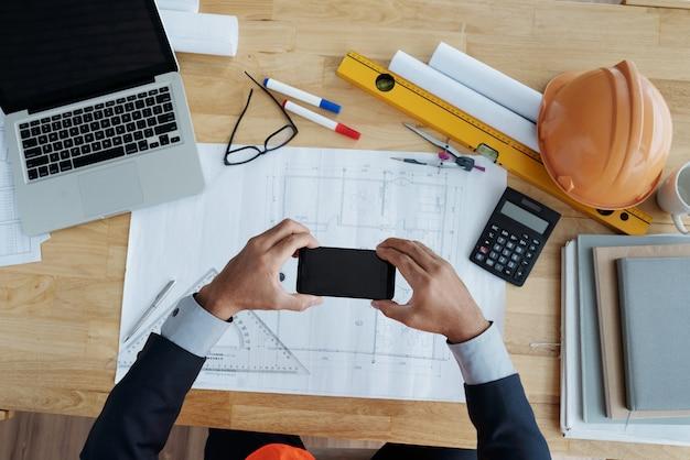 Mains d'homme méconnaissable tenant un smartphone sur un dessin technique