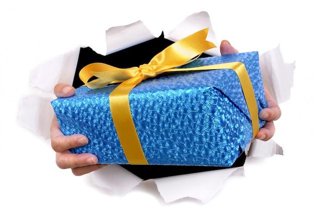 Mains d'homme offrant ou donnant un cadeau à travers le fond de papier blanc déchiré