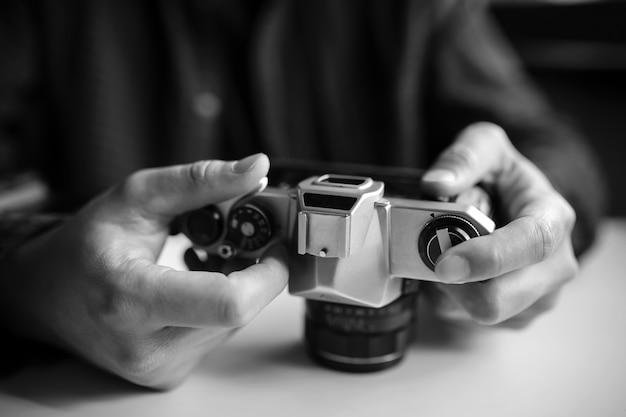 Les mains de l'homme ont mis en place un appareil photo argentique rétro. noir et blanc