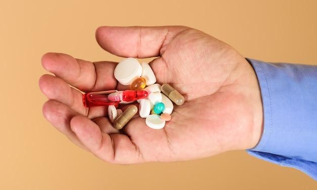 Mains d'homme avec des pilules sur fond orange.