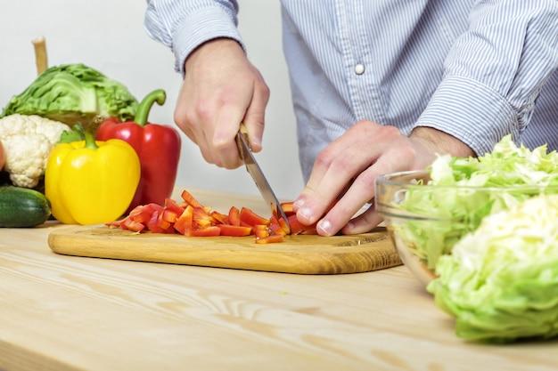 Mains d'un homme poivron rouge haché pour salade sur une planche, gros plan