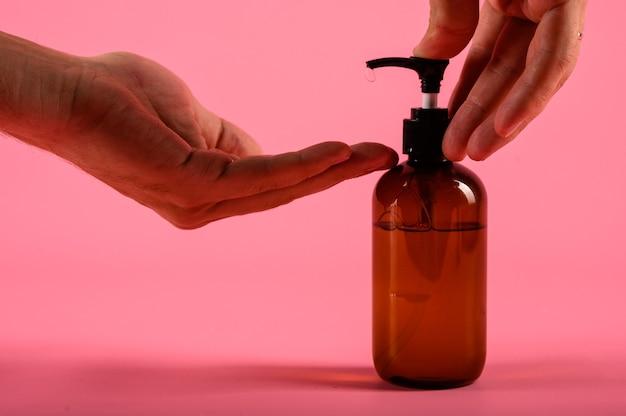 Mains de l'homme poussant la bouteille en plastique de la pompe isolé sur mur rose