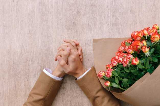 Des mains d'homme précis avec des paumes croisées et un bouquet de roses en papier kraft