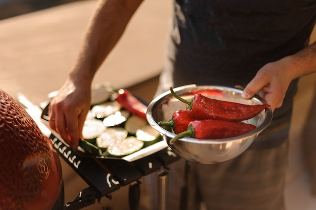 Mains d'homme préparant du poivron rouge frais pour grillades
