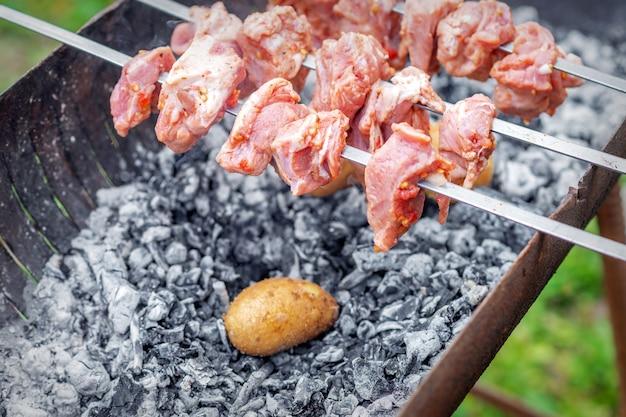 Des mains d'homme préparent de la viande de barbecue avec des pommes de terre sur une brochette de grill en feu à l'extérieur. concept de préparation de nourriture rustique de style de vie