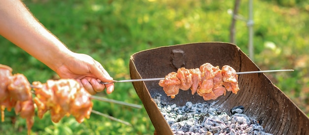 Les mains de l'homme préparent la viande de barbecue