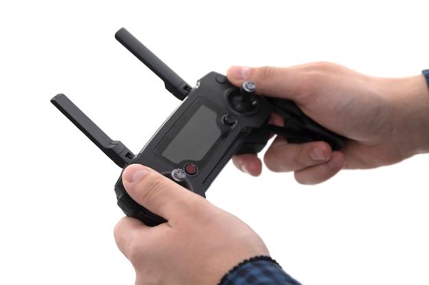 Mains de l'homme qui tient la télécommande du quadcopter sur un blanc