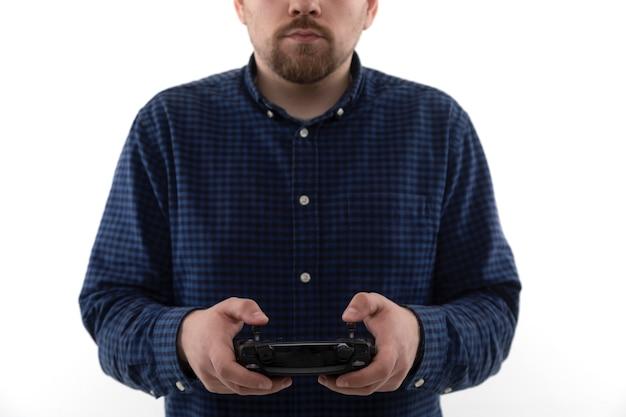 Mains de l'homme qui tient la télécommande du quadcopter
