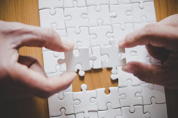 Mains d'homme reliant la pièce de puzzle de couple au bureau