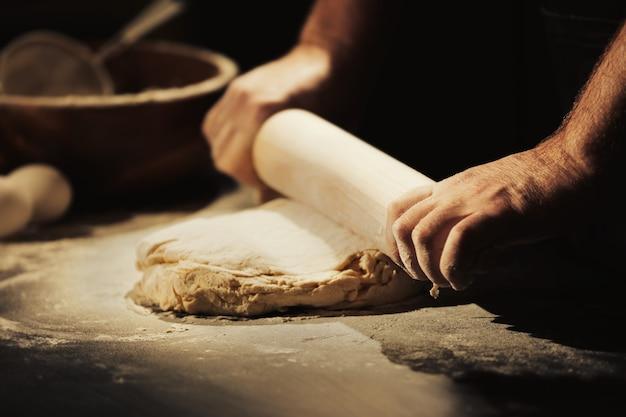 Mains d'homme roulant la pâte dans la cuisine