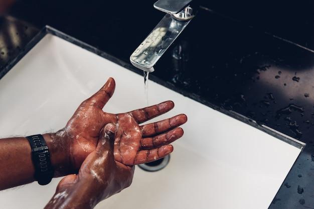 Les mains de l'homme se frottant avec du savon et de l'eau dans les éviers
