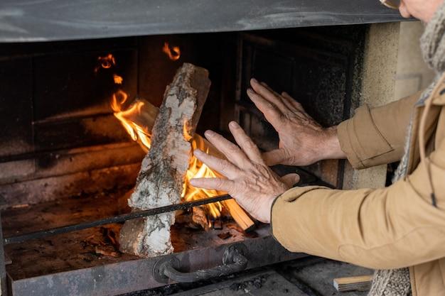 Mains d'un homme senior en veste marron debout près d'une cheminée avec du bois de chauffage tout en se réchauffant par une fraîche journée d'automne dans une maison de campagne