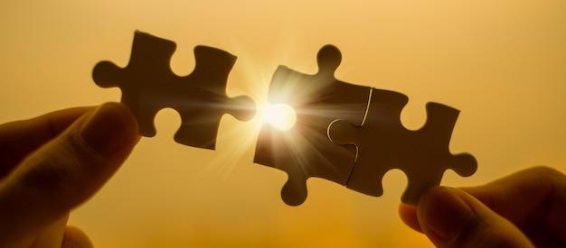 Mains d'homme de silhouette reliant la pièce de puzzle contre l'effet de la lumière du soleil