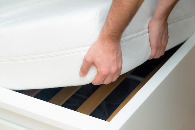 Mains d'homme soulevant le matelas dans la chambre. en regardant le cadre de lit.