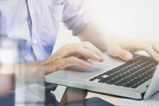 Les mains de l'homme tapant sur le clavier de l'ordinateur portable.