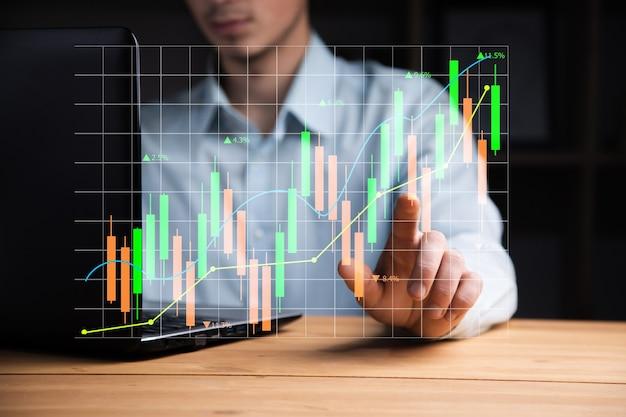 Mains d'homme tapant le clavier pour rechercher le marché boursier