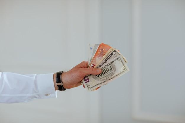 Les mains de l'homme tenant de l'argent comme l'euro et le dollar