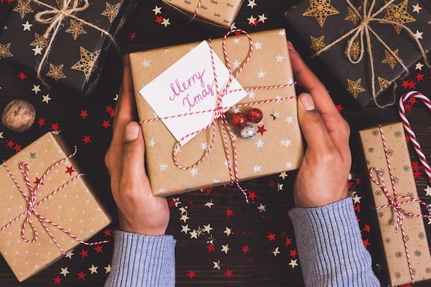 Mains d'homme tenant une boîte de cadeau de vacances de noël avec carte postale joyeux noël sur la table de fête décorée
