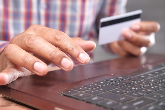 Mains d'homme tenant une carte de crédit et à l'aide du clavier shopping en ligne