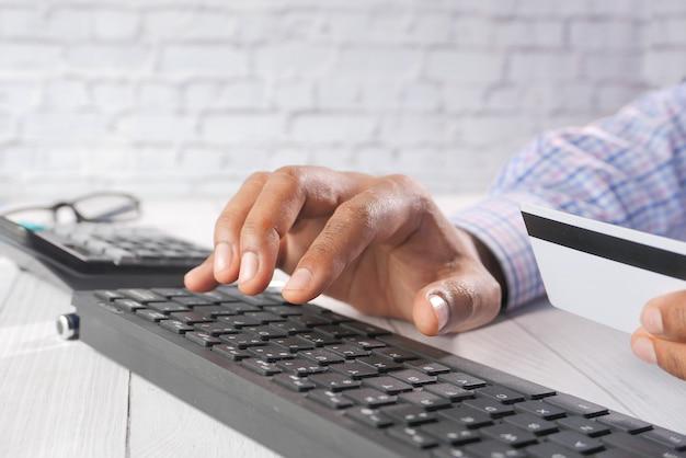 Mains d'homme tenant une carte de crédit et utilisant le clavier pour faire des achats en ligne.