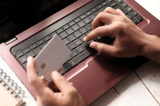 Mains d'homme tenant une carte de crédit et utilisant un ordinateur portable pour faire des achats en ligne.