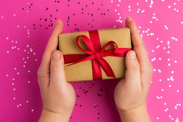 Mains d'homme tenant des coffrets cadeaux marron avec des rubans rouges. fond rose avec des confettis multicolores. style plat