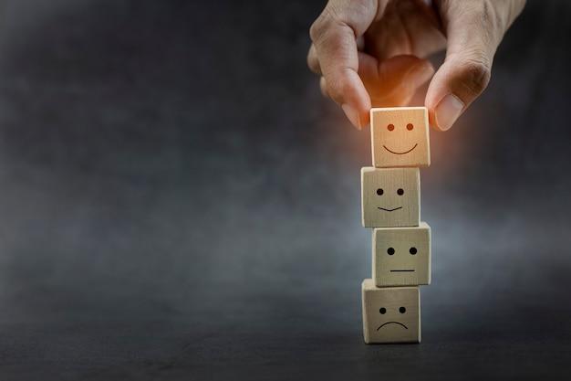 Mains d'homme tenant l'icône de visage souriant sur le cube en bois sur le fond noir