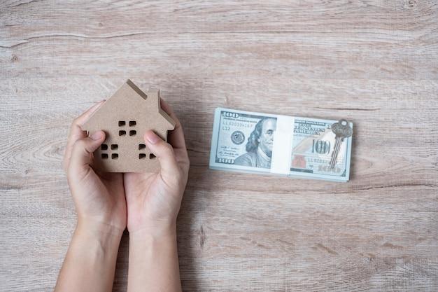 Mains d'homme tenant le modèle de maison en bois à côté de l'argent du dollar américain