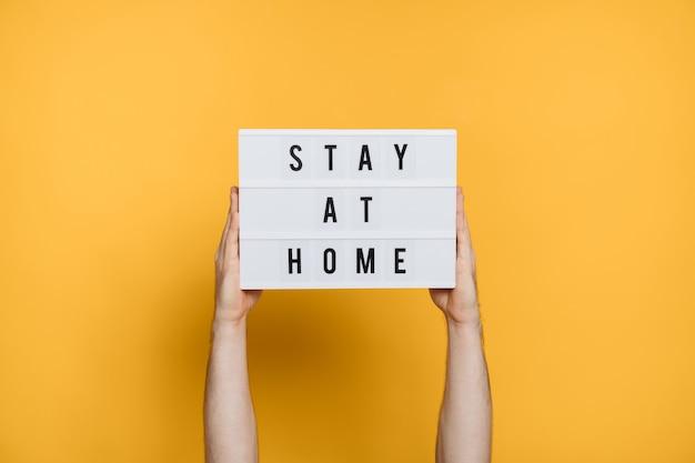 Les mains de l'homme tenant une pancarte blanche avec texte stay home sur fond jaune. campagne de médias sociaux restez à la maison pour la prévention du coronavirus ou du covid-19